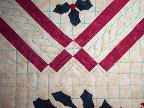 here is some of the quilting on the Christmas Baltimore Album quilt.  I decided to use a tone on tone yellow King Tut thread for the quilting on the red sashing.  I think it sets it off well, the red thread would have just disappeared in it.