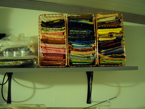 on the opposite side of the wall these wire baskets hold fabric that is mostly prints, most of these again in the size range of a fat quarter.