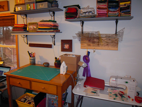 my work table and sewing machine, rulers on a rack above - photo on the wall is a small photo of the grandkids from 5 years ago I think - I need to update that with a newer photo.  Under the work table are four canvas boxes with patterns, freezer paper, one just with Dear Jane fabric (red and the top that is finished to the 9 rows right now)  The purple ribbon on the wall is one I won for best of show at the local county fair about 10 years ago? for the double wedding ring quilt with flower applique border.