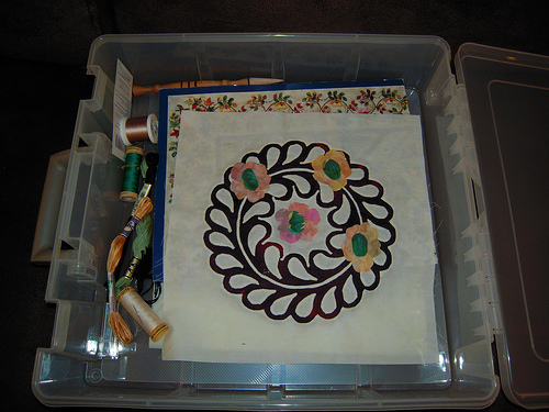 sitting in it's storage box.  I am auditioning these flowers right now - I'm not sure if I like the colors and might go brigher.  The centers of the flowers could be embroidered also if desired in a green satin stitch.  I'm not sure, I will look at it this evening when we get back home and decide.